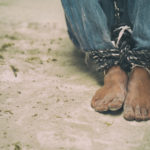 Hopeless man feet tied together with rope